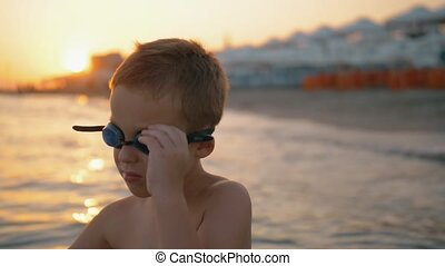 Child in goggles is going to bathe at sunset