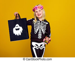 child in halloween costume isolated on yellow with shopping bag