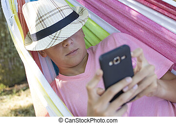 child in hammock with mobile phone