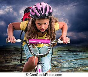 Child in helmet ride hard on bike to mountain.