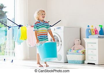 Child in laundry room with washing machine or tumble dryer. ...