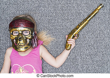 child in mask of pirate with gun
