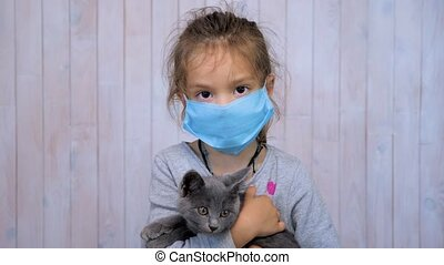Child in medical mask hugging kitten while looking at camera. Safety is the key to health. Girl with a kitten in a disposable mask. Combating threats posed by epidemics and antimicrobial resistance