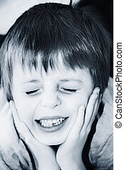 Child in pain holds head in hands.