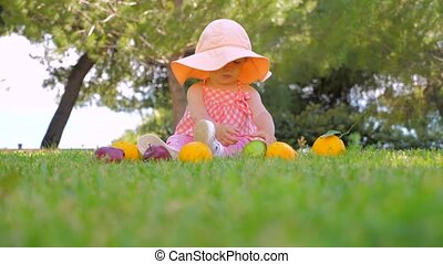 Child in panama having fun outdoor on back yard. Happy childhood concept. Baby girl playing with fruits outdoor. Toddler sitting on green grass waiting for mother.