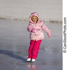 Child in Pink Ice Skating - Child in pink ice skating and...