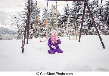 child in playground in winter