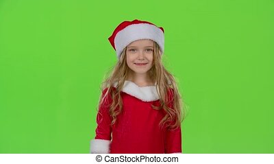 Child in red Christmas caps send air kisses. Green screen....
