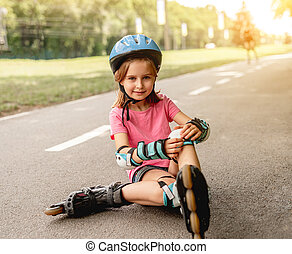 Child in roller skates sitting on alley