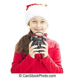 child in Santa hat holding alarm clock