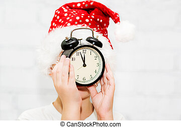 Child in santa hat keeps alarm clock, focus on a clock.