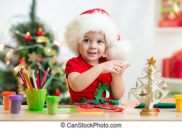 child in Santa hat making christmas tree of plasticine