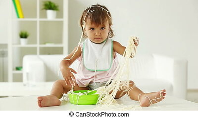 Child in spaghetti - Female toddler sitting on the table and...