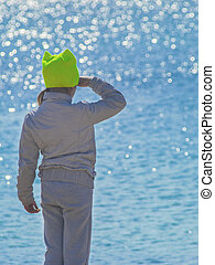 Child in sports clothes looking into the ocean