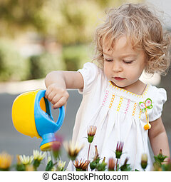 Beautiful child watering spring flowers against green natural background
