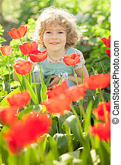 Portrait of happy child in spring flower garden