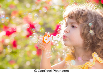 Child in spring - Happy child blowing soap bubbles outdoors ...