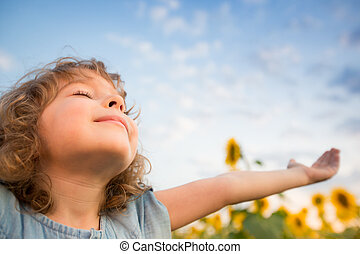 Child in spring - Happy child outdoors in spring sunflower...