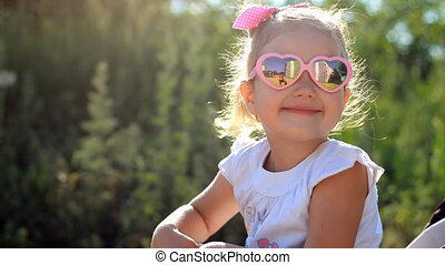 Child in sunglasses is sitting in a stroller and sends air kisses at sunset.