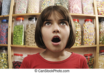 child in sweet shop looking in awe at jars of sweets