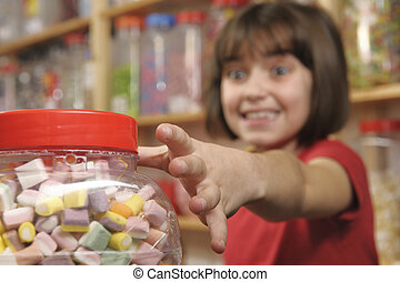 child in sweet shop - young girl grabbing a jar of sweets in...