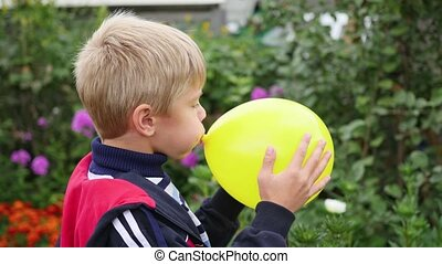 child in the garden inflate a yellow balloon