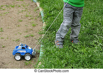 Child in the grass with the machine.