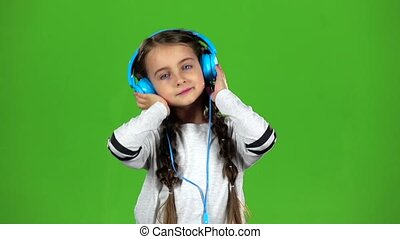 Child in the headphones is listening to music. Green screen....