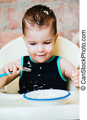 child in the kitchen eating vermicelli with milk