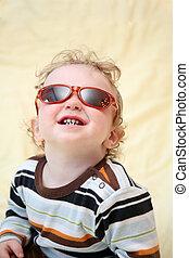 child in the sunglasses looks upward
