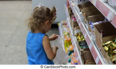 Child in the supermarket buys candies and sweets. Shopping store