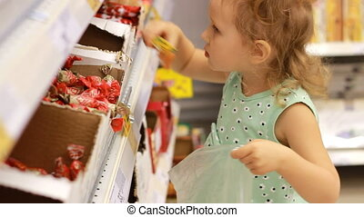 Child in the supermarket buys candies and sweets. Shopping...