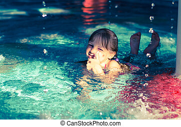 child in the water with thumb up