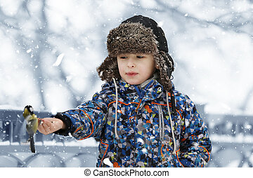 Child in the winter. Boy in winter clothes feeds a bird