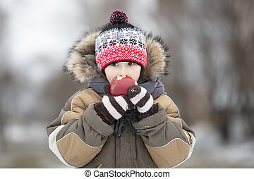 Child in the winter with fruit. Boy eating a red apple