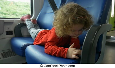 Child in train looks at smartphone