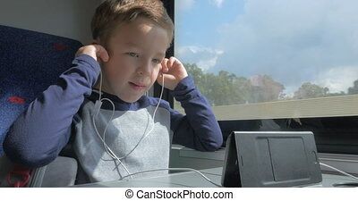 Child in train talking on mobile using hands free set - Boy...