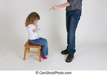mom pointing finger at little girl for being naughty.