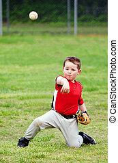 Child in uniform throwing baseball