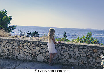 child in white dress looking to the sea