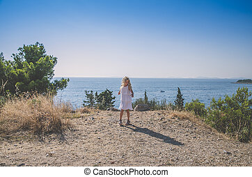 child in white dress looking to the sea and dancing