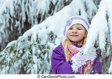child in winter forest having fun