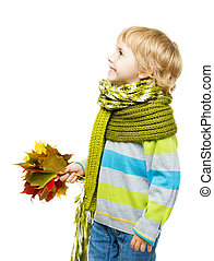 Child in woolen scarf holding maple leaves