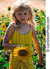 child in yellow sunflower field