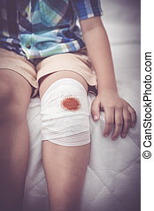 Child injured. Wound on the child's knee with bandage....