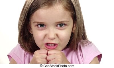 Child is angry, she is very nervous. . White background. Close up. Slow motion