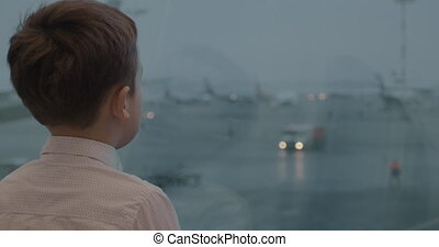 Child is attracted with airport view in the window