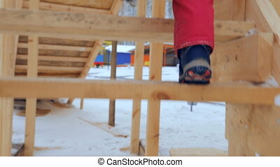 Child is climbing up slide stairs at playground