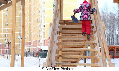 Child is climbing up slide stairs at playground