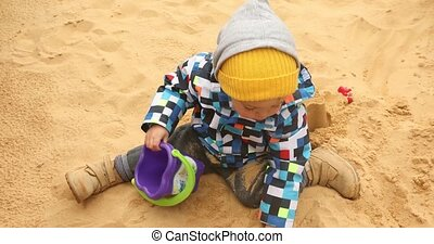 Child is digging the sand coldly - Portriat little boy...